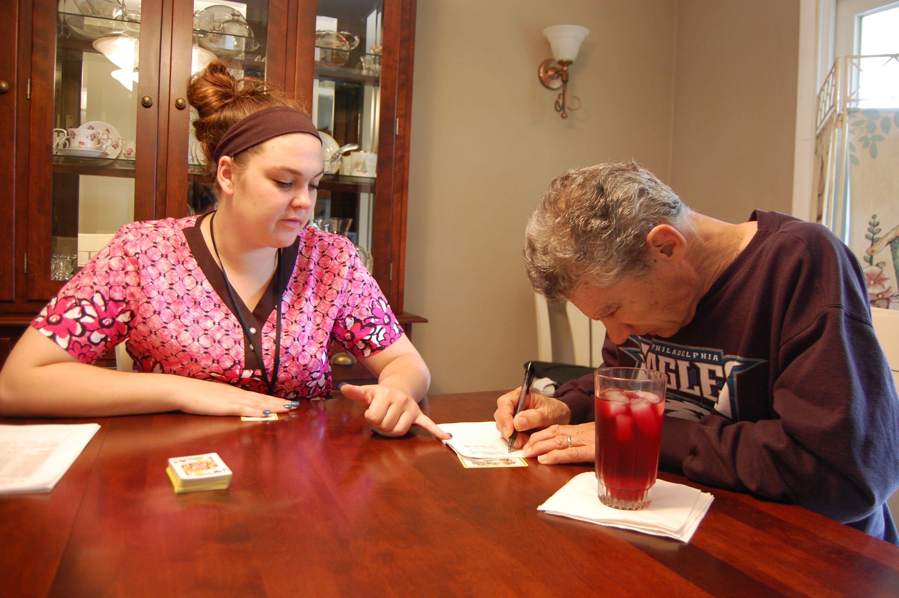 Woman helping man write